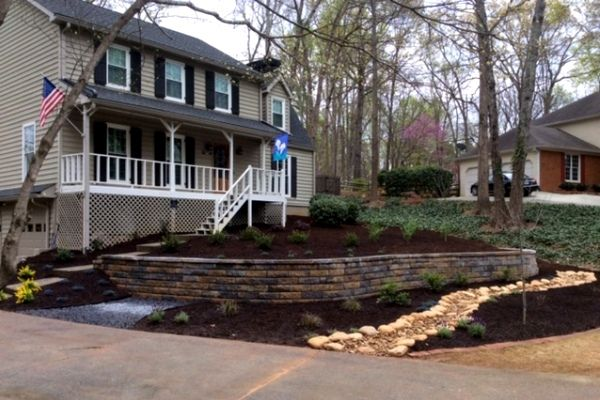 Terraced front yard with retaining wall and river rock drainage